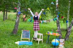 Schoolgirl child kid girl stay on chair with her hands above hea Royalty Free Stock Photo