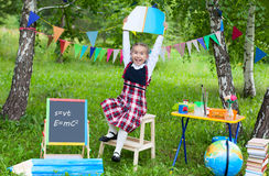 Schoolgirl child kid girl stay on chair holding book notebook ab. Ove head , classroom outdoors, happy smile stock images