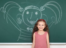 Schoolgirl child in red striped dress drawing happy man on green chalkboard background, summer school vacation concept Royalty Free Stock Photography