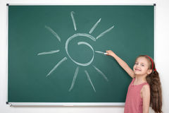 Schoolgirl child in red striped dress drawing sun on green chalkboard background, summer school vacation concept Royalty Free Stock Images