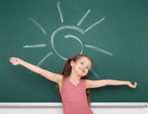 Schoolgirl child in red striped dress drawing sun on green chalkboard background, summer school vacation concept Royalty Free Stock Image
