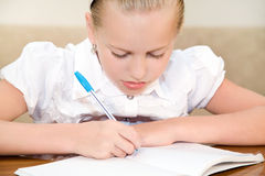 Schoolgirl child writes in a notebook. Child girl discontentedly does the lessons Royalty Free Stock Image
