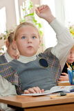Schoolgirl in the classroom raises hand Stock Photo