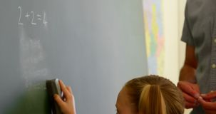 Schoolgirl cleaning chalkboard with a duster in a classroom at school 4k. Side view of Caucasian schoolgirl cleaning chalkboard with a duster in a classroom at stock footage