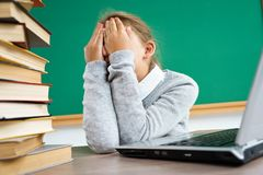 Schoolgirl closed her eyes and crying. Photo of little girl in classroom around books. Education concept royalty free stock photo
