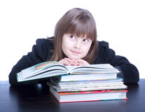 Schoolgirl. Cool schoolgirl in black uniform sitting at a table in front of her stack of books she reads Stock Photography