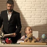 Schoolgirl and dad with busy faces hold bear and book Stock Photos