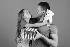 Schoolgirl and dad hold present box and white teddy bear. Girl and men with happy faces on red background. Childhood, surprise gift and family concept royalty free stock photo