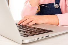 Schoolgirl at desk with laptop Royalty Free Stock Photos