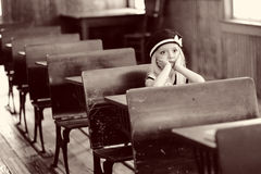 Schoolgirl in detention. A young schoolgirl sits alone behind an old-fashioned wooden desk in a school classroom waiting to be released from detention Stock Photo