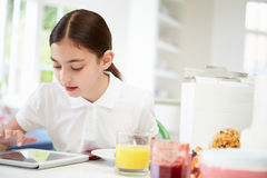 Schoolgirl With Digital Tablet At Breakfast Stock Photo