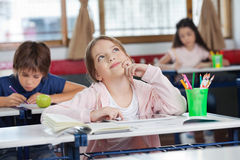 Schoolgirl With Digital Tablet At Desk Looking Up. Thoughtful schoolgirl with digital tablet looking up while friends studying in background at classroom Stock Image