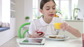 Schoolgirl With Digital Tablet And Mobile Eating Toast stock footage