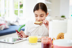 Schoolgirl With Digital Tablet And Mobile Eating Toast Royalty Free Stock Images