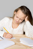 Schoolgirl doing difficult homework Stock Photo