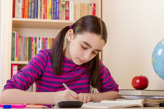 Schoolgirl doing her homework Stock Photography