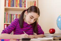 Schoolgirl doing her homework Stock Photography