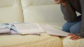 Schoolgirl doing her homework on the sofa stock video footage