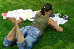 Schoolgirl doing homework. A shoolgirl doing her homework outdoors Royalty Free Stock Image