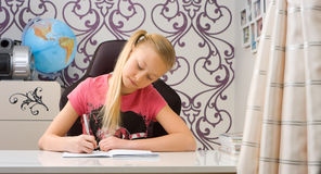 Schoolgirl doing homework at home Stock Images