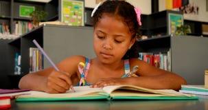Schoolgirl doing homework in library 4k stock video