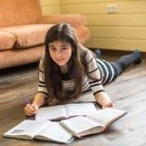 Schoolgirl doing homework lying on the floor Royalty Free Stock Images