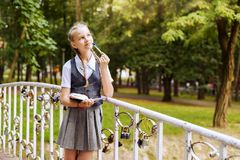 Schoolgirl doing homework in park and dreaming royalty free stock photos