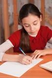 Schoolgirl doing homework Stock Images