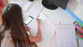 Schoolgirl doing homework at the table leafs through book. Girl makes lessons stock video