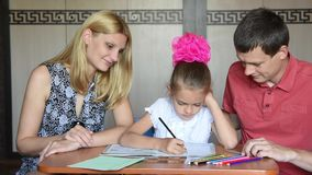 Schoolgirl doing homework with their parents smile looked into the frame stock footage