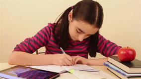 Schoolgirl doing homework using tablet pc stock footage