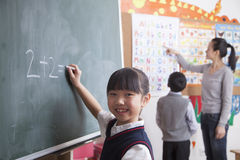Schoolgirl doing math equation on the black board Royalty Free Stock Photo