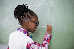 Schoolgirl doing mathematics on chalkboard in classroom royalty free stock photography