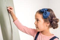 Schoolgirl drawing on blackboard Stock Images