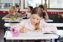 Schoolgirl Drawing In Book At Classroom. Cute little schoolgirl drawing in book with classmates in background at classroom royalty free stock photo
