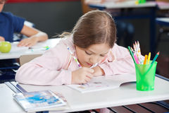 Schoolgirl Drawing In Book At Desk. Little schoolgirl drawing in book at desk in classroom stock photography