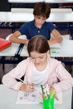 Schoolgirl Drawing At Desk In Classroom Stock Image