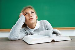 Schoolgirl dreaming or thinking of something while sitting at the desk with open book. Education concept royalty free stock image