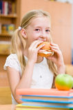 Schoolgirl eating fast food Royalty Free Stock Photos