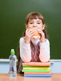 Schoolgirl eating fast food while having lunch Stock Photo