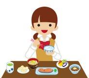 Schoolgirl eating Japanese breakfast- Long Sleeved.  Royalty Free Stock Photo