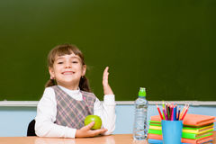 Schoolgirl elementary school raising hands knowing the answer to question Royalty Free Stock Image