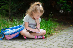 Schoolgirl of elementary school sits having crossed legs on a grass and something writes to notebook. Stock Photo
