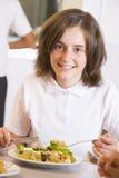 Schoolgirl enjoying her lunch in school Royalty Free Stock Images