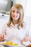 Schoolgirl enjoying her lunch in school Stock Photography