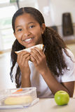 Schoolgirl enjoying her lunch in school cafeteria