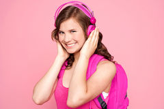 Schoolgirl enjoying music and smiling Royalty Free Stock Images
