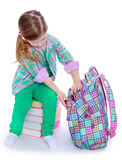 Schoolgirl examines a backpack Stock Photos
