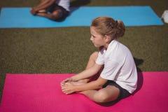 Schoolgirl exercising in schoolyard Stock Photo