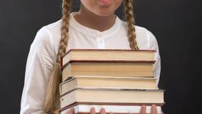 Schoolgirl in eyeglasses holding books against blackboard, education, geek